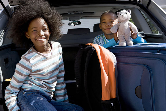 Two kids smiling from back of family SUV with luggage and toy