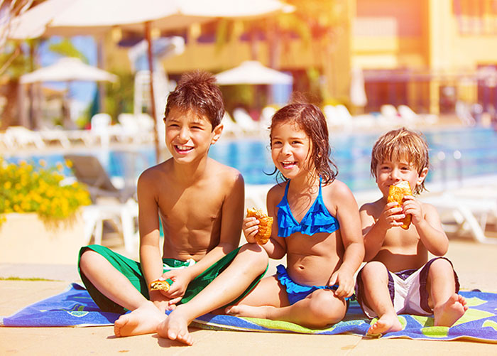 kids sitting on a towel smiling next to pool eating